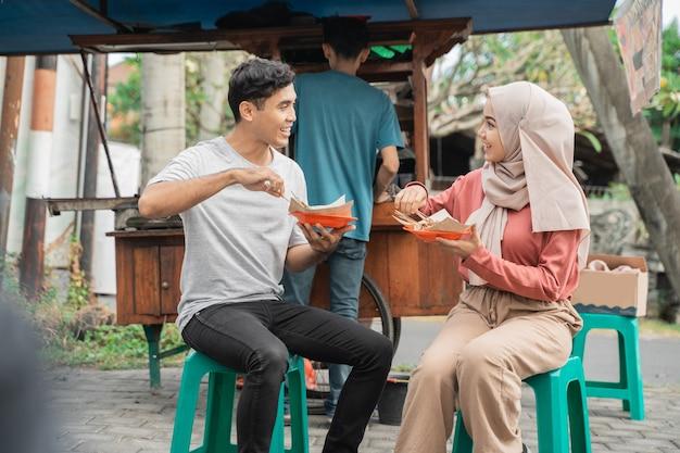 Casal gosta de comer frango satay que comprou de um vendedor de comida de rua na indonésia