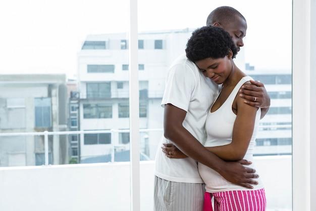 Casal grávida abraçando um ao outro em casa