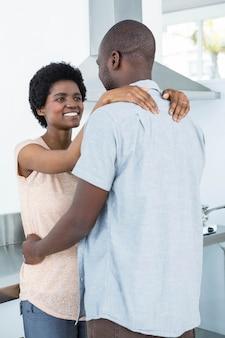 Casal grávida abraçando um ao outro na cozinha em casa