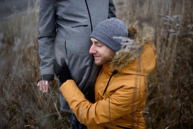 Casal grávida está andando fora da cidade no final do outono.