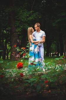 Casal grávida feliz no parque de verão