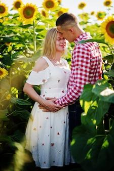 Casal grávida no campo de girassóis. momentos de gravidez