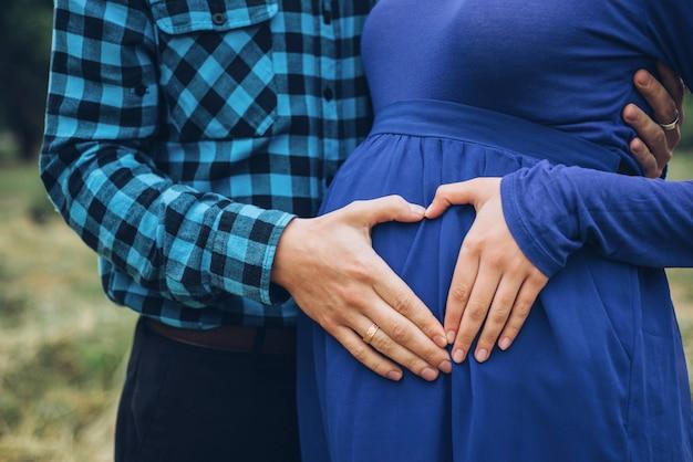 Casal grávida segurando a barriga com coração