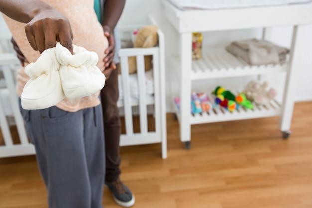 Casal grávida segurando sapatos de bebê branco perto do berço