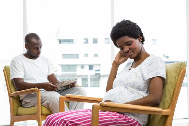 Casal grávida sentada na cadeira em casa