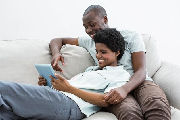 Casal grávida usando tablet digital no sofá na sala de estar