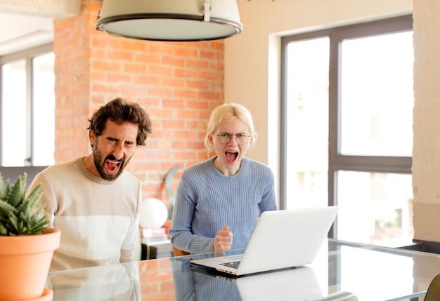 Casal gritando agressivamente, parecendo muito zangado, frustrado, indignado ou irritado, gritando não