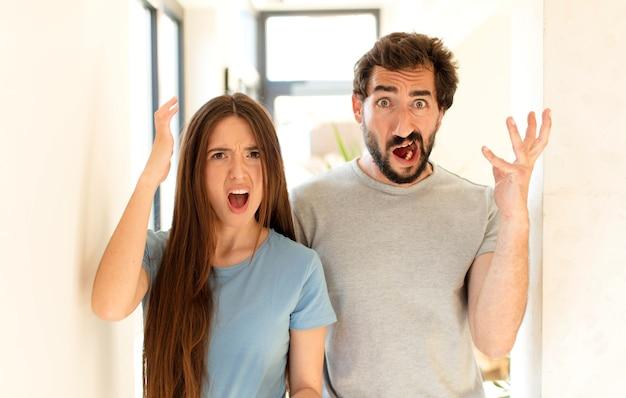 Casal gritando com as mãos para o alto, sentindo-se furioso, frustrado, estressado e chateado