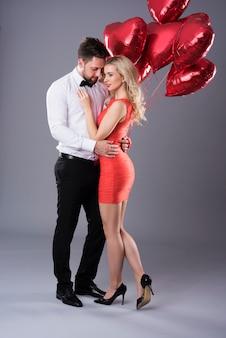 Casal heterossexual com balões vermelhos em formato de coração