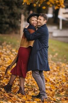 Casal heterossexual feliz se abraça enquanto caminha no parque da cidade no dia de outono.