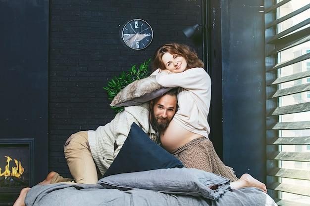 Casal heterossexual lindo jovem e uma mulher grávida brigando com almofadas na cama no quarto em casa