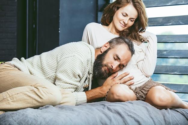 Casal heterossexual lindo jovem e uma mulher grávida na cama no quarto em casa
