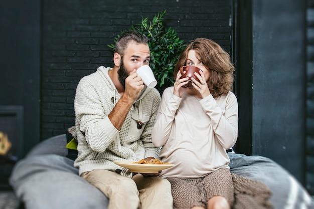 Casal heterossexual lindo jovem e uma mulher grávida tomando café da manhã na cama, no quarto de casa