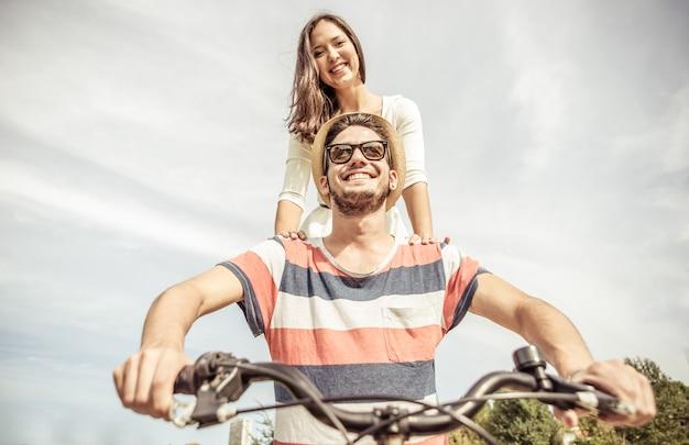 Casal hipster andando de bicicleta pelas ruas
