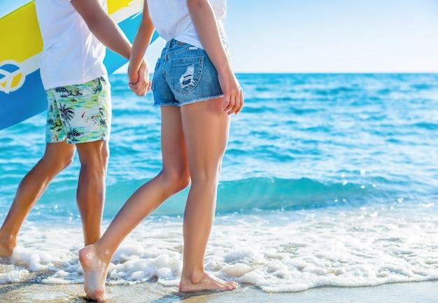 Casal hispânico caminha na praia com prancha de surf se divertindo ao ar livre