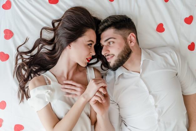Casal homem e mulher apaixonada na cama com formas de coração vermelho em casa