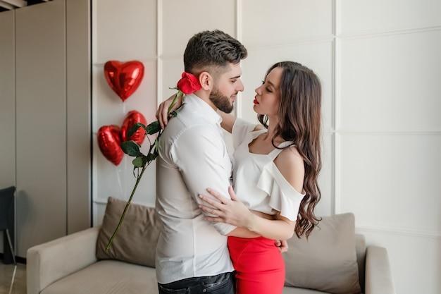 Casal homem e mulher apaixonada por rosa vermelha e balões em forma de coração em casa