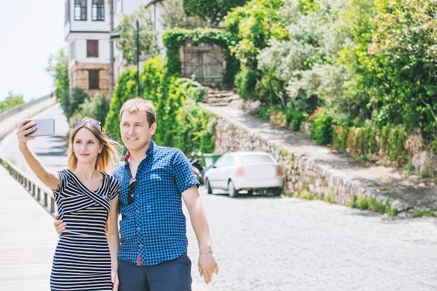 Casal, homem e mulher, caminhando pela cidade e tirando selfies românticos e felizes juntos