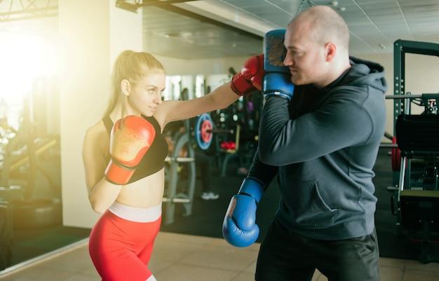 Casal homem e mulher de boxe em luvas de boxe e roupas esportivas no ginásio.