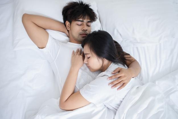Casal homem e mulher dormindo na cama