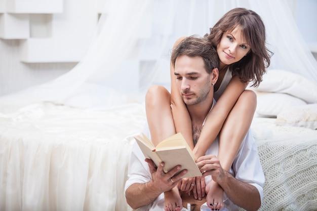 Casal homem e mulher em casa, na cama com um livro e uma bebida quente. amor terno nas relações familiares
