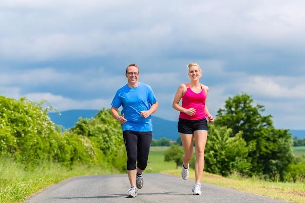 Casal, homem e mulher fazendo corrida ou esporte ao ar livre para se exercitar em uma rua rural