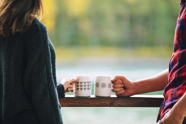 Casal homem e mulher jovem linda feliz na varanda de uma casa de madeira na natureza com canecas com bebidas quentes.