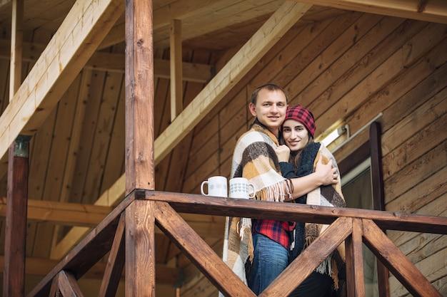 Casal homem e mulher jovem linda feliz na varanda de uma casa de madeira na natureza com canecas de bebidas quentes