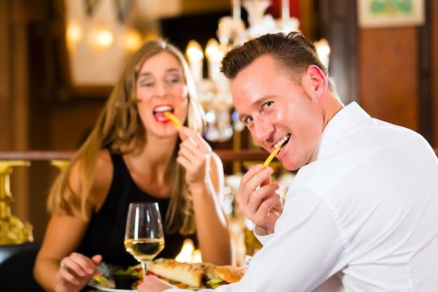 Casal, homem e mulher, um restaurante fino que comem fast-food e batatas fritas