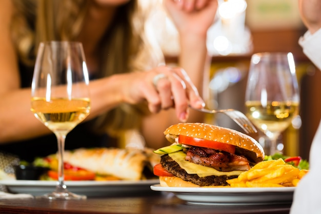 Casal, homem e mulher, um restaurante fino que comem fast-food, hambúrguer e batatas fritas, closeup