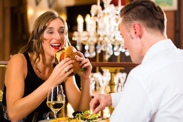 Casal, homem e mulher, um restaurante fino que comem fast-food, hambúrguer e batatas fritas