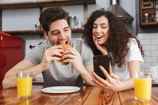 Casal, homem e mulher, usando telefone celular enquanto come hambúrguer durante o café da manhã na cozinha de casa