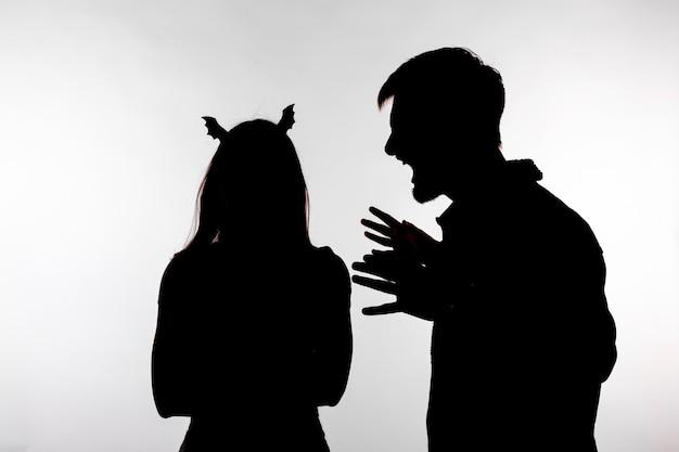 Casal homem gritando com mulher gritando disputa em silhueta de estúdio isolada no fundo branco. mulher com orelhas de morcego, dia das bruxas.