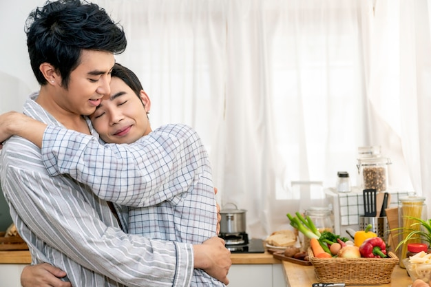Casal homossexual asiático abraço e beijo na cozinha pela manhã. conceito lgbt gay.