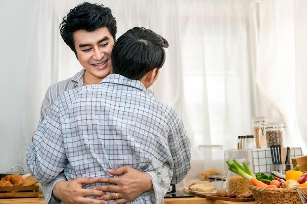 Casal homossexual asiático abraço e beijo na cozinha pela manhã
