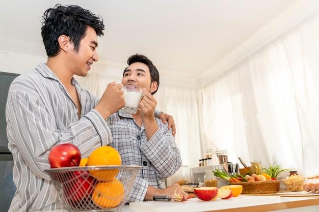 Casal homossexual asiático bebendo leite na cozinha