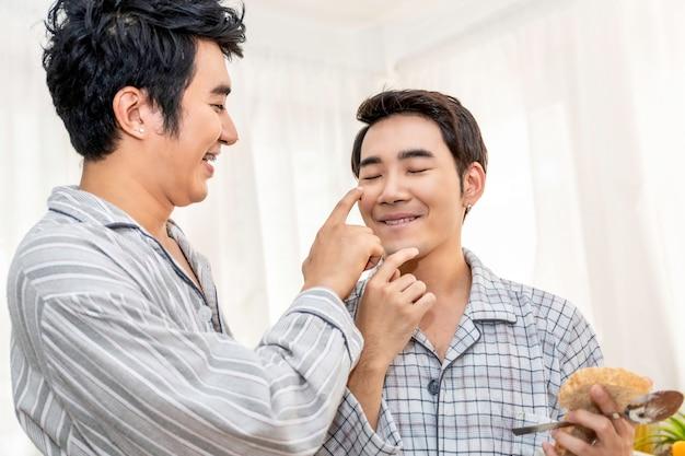 Casal homossexual asiático cozinhando o café da manhã na cozinha pela manhã. conceito lgbt gay.