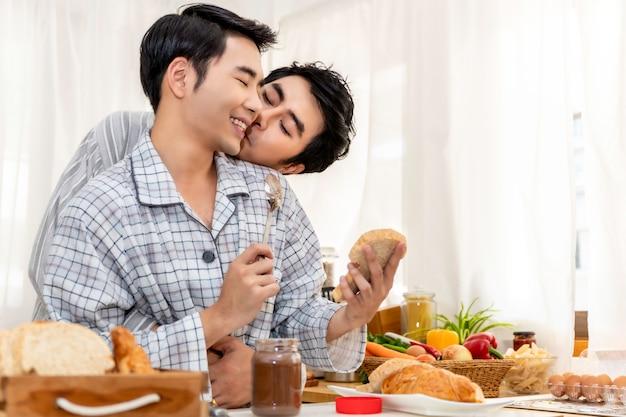 Casal homossexual asiático cozinhando o café da manhã na cozinha pela manhã
