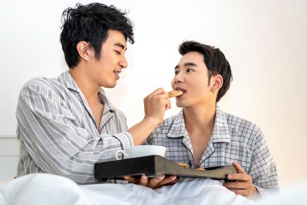 Casal homossexual asiático de pijama, tomando um café da manhã na cama. conceito lgbt gay.