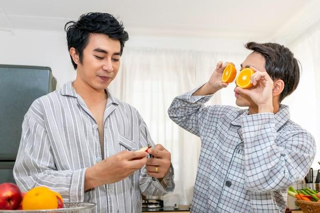 Casal homossexual asiático feliz e engraçado cozinhar salada na cozinha. conceito lgbt gay.