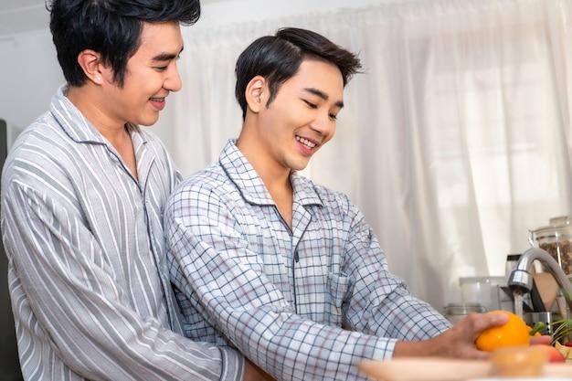 Casal homossexual asiático feliz e engraçado cozinhar salada na cozinha