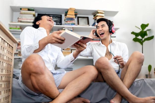 Casal homossexual asiático ri e ouve música sentado na sala de estar em casa