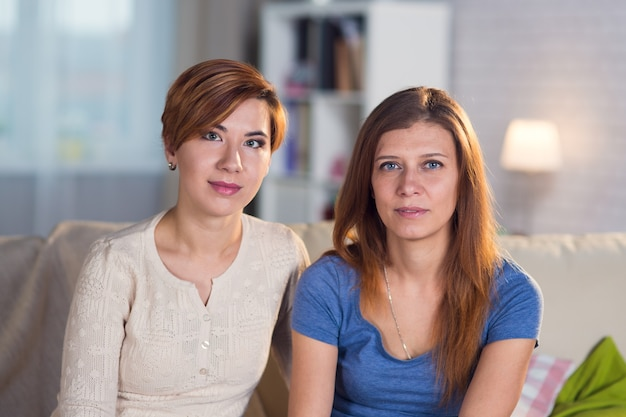 Casal homossexual de lésbicas em casa no sofá se abraçando e se divertindo