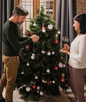 Casal idoso a decorar a árvore de natal