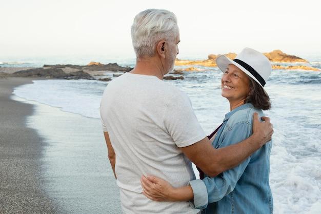 Casal idoso abraçado aproveitando o dia na praia