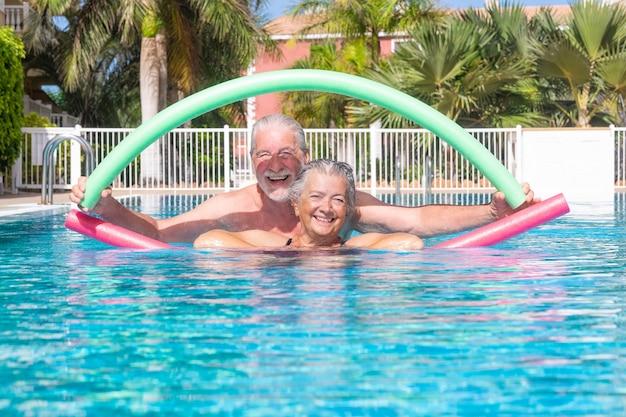 Casal idoso alegre fazendo exercícios na piscina com macarrão de natação.