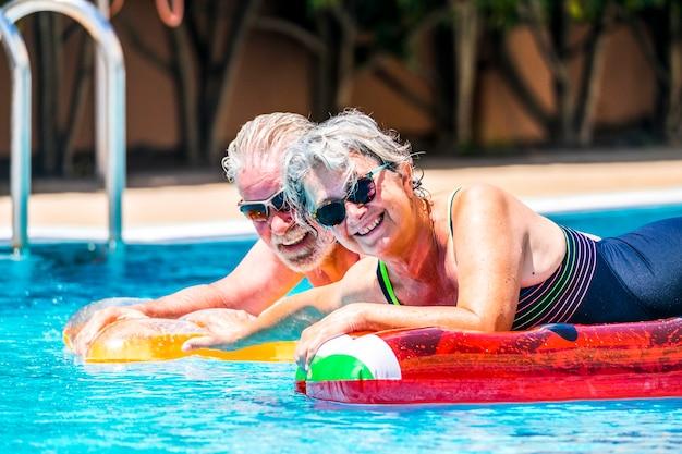 Casal idoso aposentado e mulher sênior desfrutando da atividade de lazer na piscina de verão deitar-se no colchão inflável colorido da moda lilos na água azul em casa ou atividade de hotel