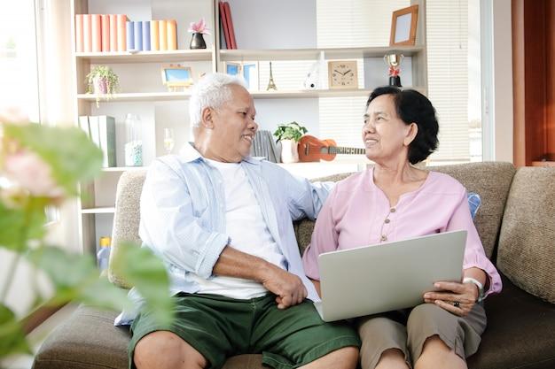 Casal idoso asiático sentado no sofá usando laptop
