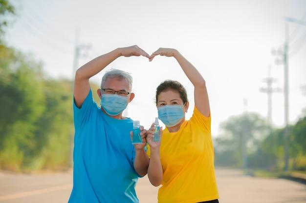 Casal idoso asiático usa máscara facial, usa gel de álcool para limpar as mãos protege o coronavírus covid 19, idoso, mulher, seguro de idade