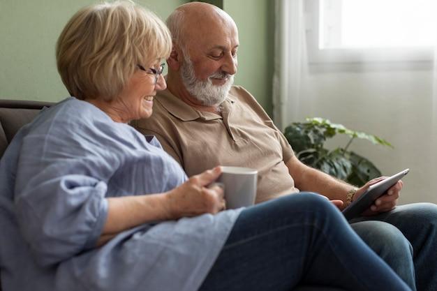 Casal idoso com foto média dentro de casa
